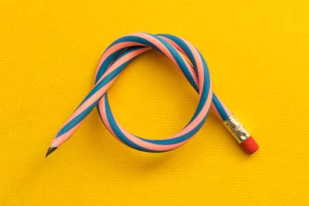 Flexible pencil . Isolated on yellow background. Фото со стока