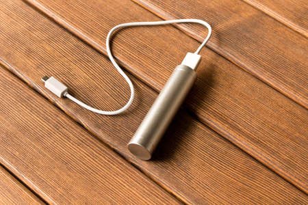 Silver powerbank with connector on wooden table Stock Photo