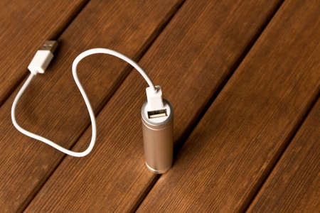 Silver powerbank with connector on wooden table Imagens