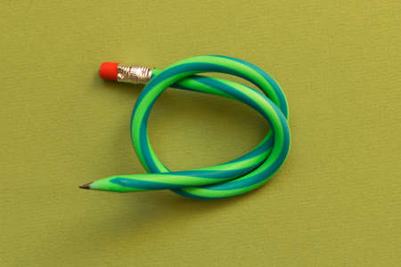 Flexible pencil . Isolated on dark green background.