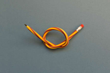 Flexible pencil . Isolated on light background. Bending pencil. Imagens