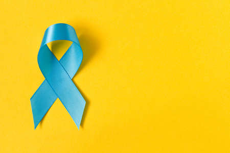 Blue ribbon.  Isolated on yellow background with empty space for text. Close up Stok Fotoğraf