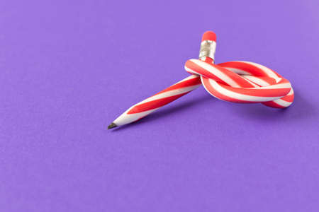 Flexible pencil . Isolated on purple background. Bending pencil