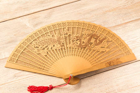 Beautiful wooden fan on wooden table