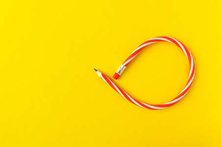 Flexible pencil . Isolated on yellow background. Bending pencil