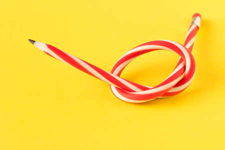 Red and white flexible pencil. Isolated on yellow background