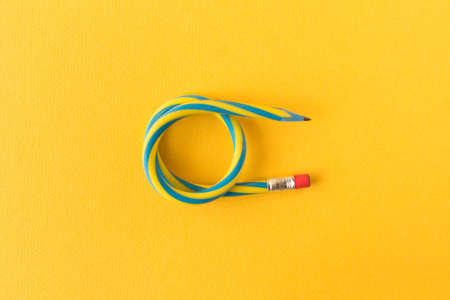 Flexible pencil. Isolated on yellow background. Bending pencil