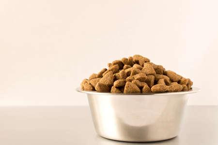 Recipiente con comida para perros sobre un fondo claro. De cerca