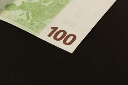 100 Euro banknote on a dark background. Close up. The concept of savings