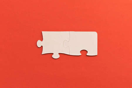 White jigsaw puzzles on red background. The concept of development of thinking. The concept of teamwork