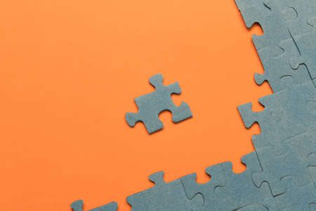 Abstract background of many puzzles on an orange background. The concept of teamwork