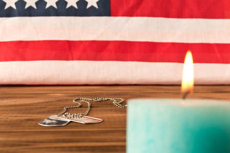 American flag and army tokens  and memorial candle on memorial day. On wooden table. Selective focus