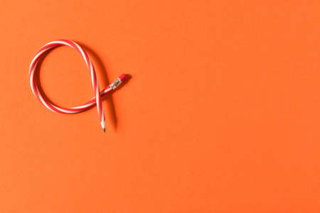 Flexible pencil. Isolated on orange background. Bending pencil