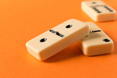 Playing dominoes on a orange table. Domino effect Stock Photo