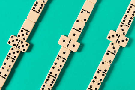 Playing dominoes on a blue table. Domino effect Stock Photo