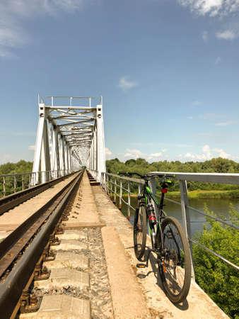 Bike on the railway bridge over the river against the blue sky
