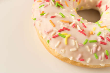 Fresh glazed donut with colorful sprinkles on a white plate 免版税图像