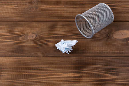 Crumpled sheet of paper and metal basket. On a wooden background Banco de Imagens