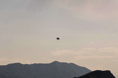 Skydiver flying far in the sky over the mountains