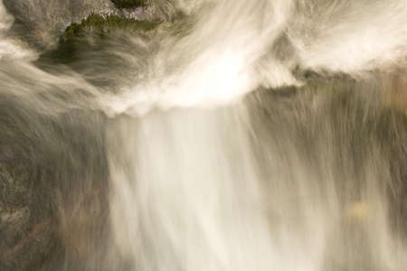 Blurred abstract background of running water. The flow of water in a mountain river Banco de Imagens