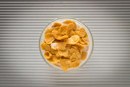 Cornflakes with milk in a plate on a silver background. The view from the top.