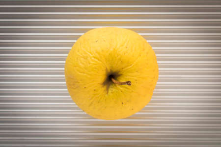 An old yellow Apple on a silver background. Stockfoto