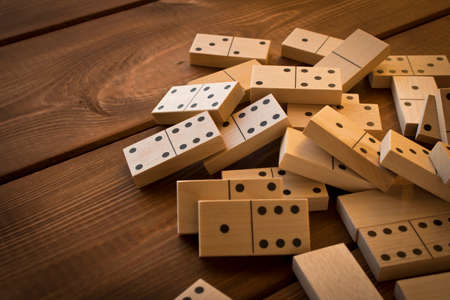 Playing dominoes on a wooden table. Leisure games concept. Domino effect.
