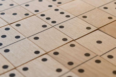 Playing dominoes on a wooden table. Leisure games concept. Domino abstract background. Selective focus.