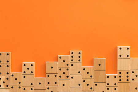 Playing dominoes on a orange table. Leisure games concept. Domino effect. Stockfoto