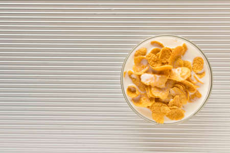 Cornflakes with milk in a plate on a silver background. Stockfoto