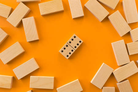Playing dominoes on a orange table. Leisure games concept. Domino effect