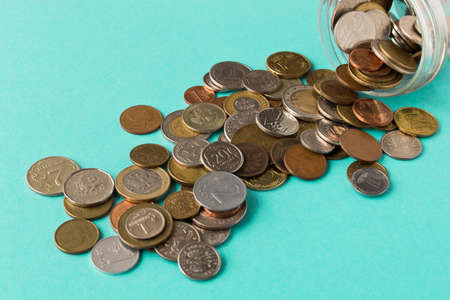 Various coins are scattered on a blue background. The concept of poverty. Selective focus