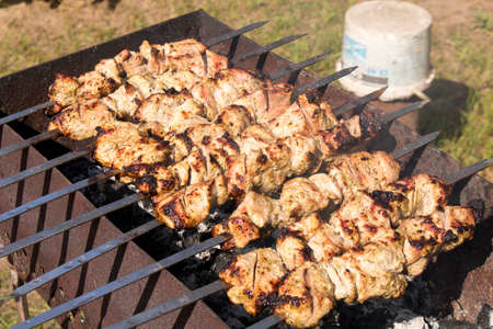 Kebab grilling on metal skewers. Meat on the grill. Close up