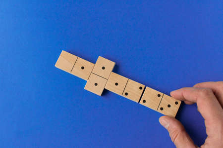 Playing dominoes on a blue background. Mans hand with domino. Leisure games concept. Domino effect
