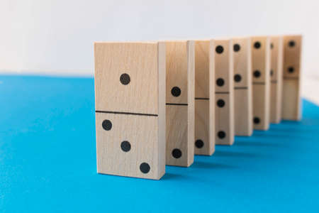 Playing dominoes on a white blue background. Leisure games concept. Domino effect
