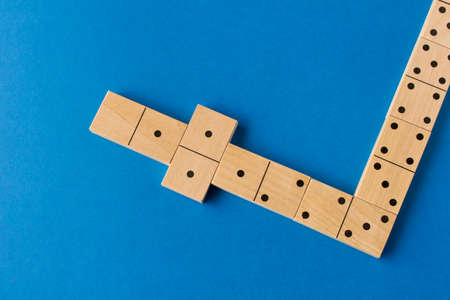 Playing dominoes on a blue background. Leisure games concept. Domino effect