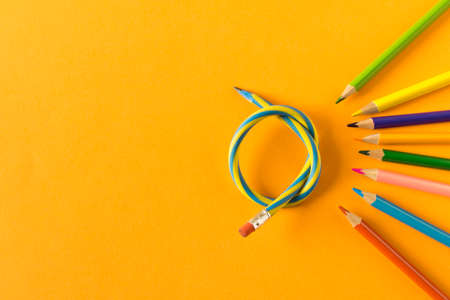 Colored pencils with one flexible pencil on orange background. The concept of flexibility in decision-making