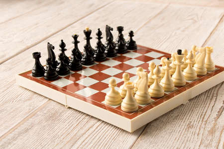 Chessboard with figures on a wooden table. Selective focus