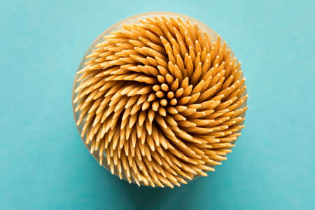 Lots of wooden toothpicks on a blue background. Abstract background for the design. The view from the top