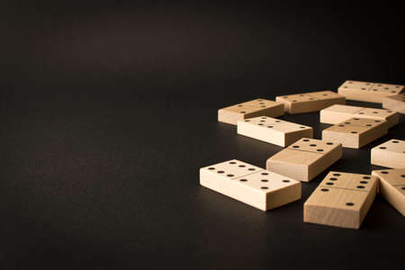 Playing dominoes on a dark background. Leisure games concept. Domino effect. Selective focus