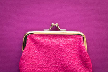 Fashionable pink wallet on a purple background. Close up