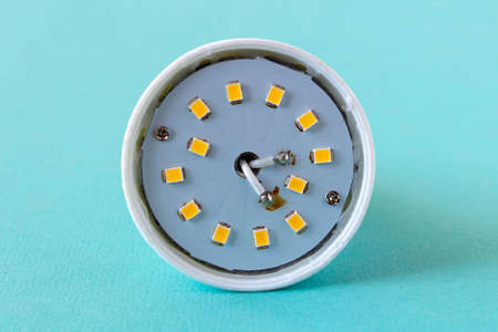 Broken led lamp on a blue background. Led lamp repair. Selective focus