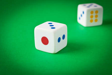 Dice on a green playing table. Close up. The concept of luck in gambling