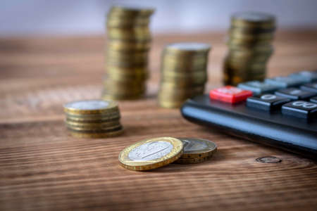 A stack of coins and a calculator on a wooden table. Concept of savings and financial accounting. Selective focus