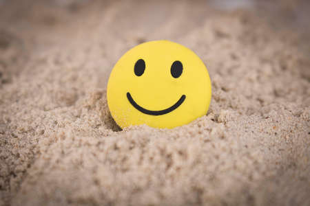 Yellow smiley face in the sand. The concept of a positive mood