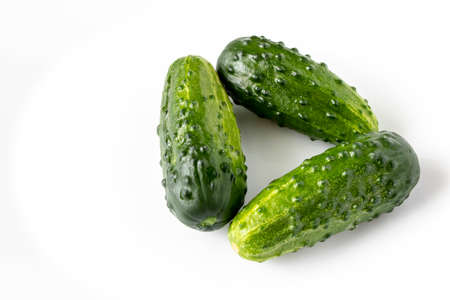 A few fresh green cucumbers on a light background. The concept of natural food. Selective focus