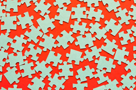Puzzle. Many puzzle pieces on a red background. The concept of collective thinking