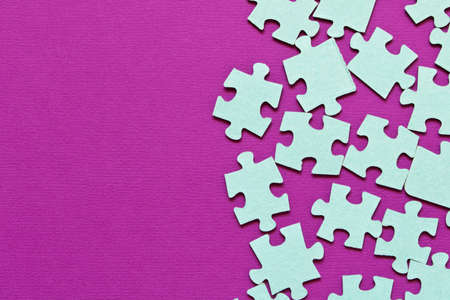 Puzzle. Many puzzle pieces on a purple background. The concept of collective thinking