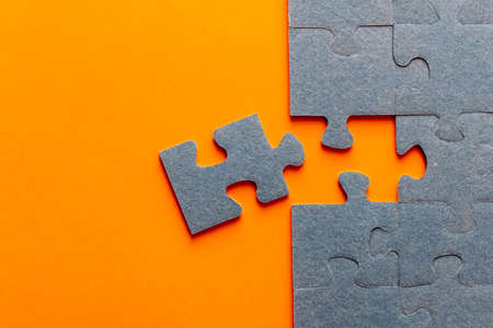 Puzzle. Many puzzle pieces on an orange background. The concept of collective thinking Imagens