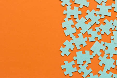 Puzzle. Many puzzle pieces on an orange background. The concept of collective thinking Banco de Imagens